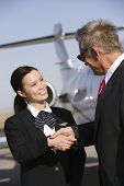 Senior business man thanking pretty Korean stewardess at airfield