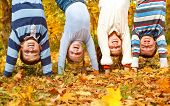 Kids group upside down in an autumn park