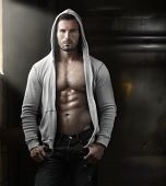 Young handsome macho man with open jacket revealing muscular chest and abs in industrial garage with