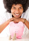 Black man with a piggybank - isolated over a white background