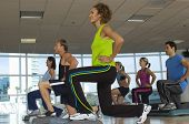 People exercising on step in aerobics class
