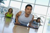 Hispanic trainer and group of people practicing yoga
