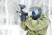 paintball extreme sport player wearing protective mask and comouflage clothing with marker gun at wi
