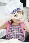pic of pry  - Little girl in hat and apron cooking in kitchen - JPG