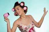 Fun portrait of an attractive woman in outsized pink haircurlers with a hairdryer in her hand posing