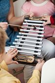 Midsection of teacher and students playing xylophone in music class
