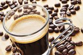 pic of hot coffee  - closeup of a cup of coffee on a wooden table with roasted coffee beans - JPG
