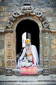 KATHMANDU, NEPAL - MAY 18: Shaiva sadhu seeks alms on the Pashupatinath Temple  on May 18, 2013 in K