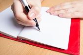 Hand Writing In Red Notebook