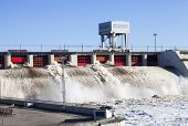 stock photo of hydroelectric power  - Spring flood water flowing on hydroelectric power station dam - JPG