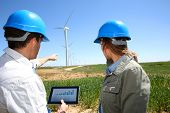 Engineers using tablet on wind turbine site