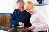 Quality of life - two elderly people sitting at home in front of the furnace, writing emails on the
