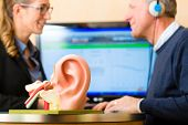 Older man or pensioner with a hearing problem make a hearing test and may need a hearing aid, in the