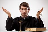 pic of rosary  - Young reverend with crucifix rosary and the Bible - JPG