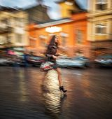Woman Walking Down The Street After A Rain