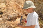 picture of paleontologist  - Young boy studing geology out in the field - JPG