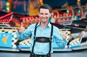 Young man wearing traditional Bavarian Lederhosen with thumbs up