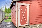 pic of red siding  - View of red small shed standing on the backyard - JPG