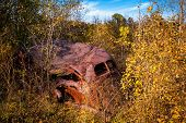 Old Abandoned Rusted Antique Car In Heavy Weeds
