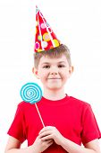 Smiling boy in red t-shirt and party hat holding colored candy - isolated on white.