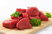 stock photo of dice  - diced raw beef meat on the cutting board - JPG