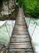 Rickety foot bridge over white water