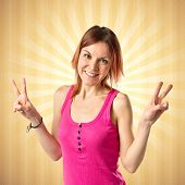 Young Woman Doing Victory Gesture Over Ocher Background