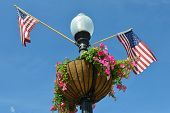 Washington D.C. - Street lamp post with United State National flags and flower pot in Georgetown.