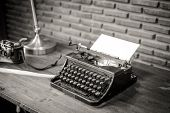 stock photo of typewriter  - Black and white of an old typewriter with paper on a wooden table photo in retro style - JPG