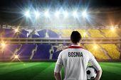 Bosnia football player holding ball against stadium full of bosnia football fans