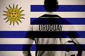 Uruguay football player holding ball against uruguay national flag