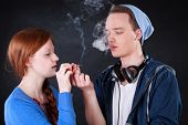 stock photo of tobacco smoke  - Horizontal view of a teenagers smoking marijuana joint - JPG