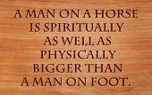 A man on a horse is spiritually as well as physically bigger than a man on foot - quote on wooden re