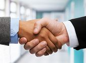 business and office concept - businessman and businesswoman shaking hands in office