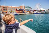 Boy on a  boat pointing (focus on boys arm)