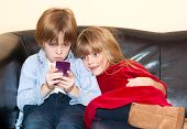 pic of snuggle  - Little boy reading a text message on a smartphone with a long face as his pretty little sister snuggles up looking over his shoulder with a smile as they relax on a sofa - JPG