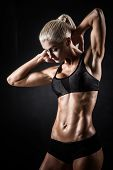 Beautiful athletic woman showing muscles on dark background