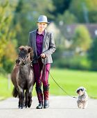 Woman walking with pony and dog