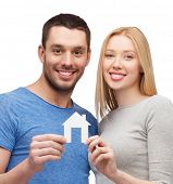real estate, family and couple concept - smiling couple holding white paper house