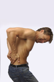 stock photo of toples  - Toples muscular man suffers from terrible lower back pain - JPG