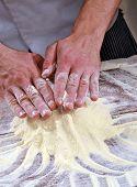 Cook preparing pizza dough.
