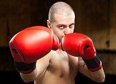 Tough boxer training in an old dark gym