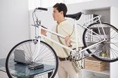 Casual businessman carrying his bicycle in his office