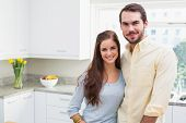 Young couple smiling at the camera at home in the kitchen