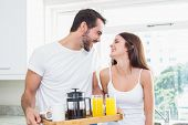 Young couple with breakfast on tray at home in the kitchen