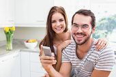 Young couple smiling at the camera man holding smartphone at home in the kitchen