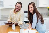 Young couple smiling at camera using technology at home in the kitchen