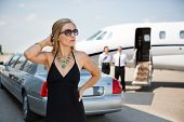 Wealthy woman in elegant dress standing against limousine and private at terminal