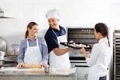 Happy male and female chefs baking in commercial kitchen