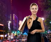 shopping, sale, gifts and holidays concept - smiling woman in evening dress with shopping bags over night city background